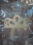 White modeling chocolate tiara formed around a plastic jar for shape, with grooves to attach edible pearls later