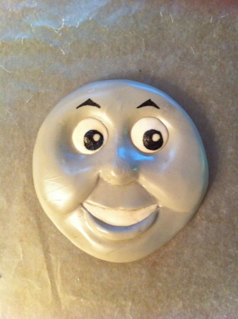 Thomas' face sculpted of tinted marshmallow fondant and decorated with food coloring pens