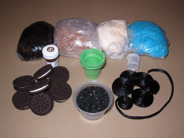 Various colors of marshmallow fondant, ice cream cone cut for smokestack, brown food coloring for woodgrain effect, cookie wheels, black sugar for coal, and licorice for train tracks