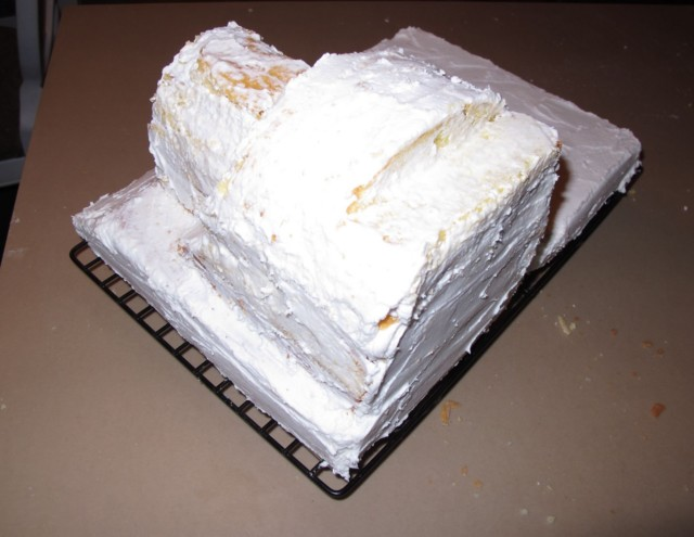 white cake cut for Thomas' body, assembled and crumbcoated together with buttercream frosting